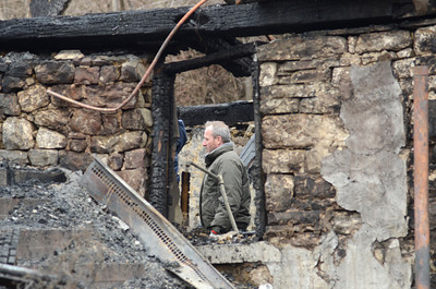 A Goodville Mutual Insurance Company Agent looks around the remains of the home at 60 S. Smith Road in Rush Township that burnt down Friday morning killing three young children.