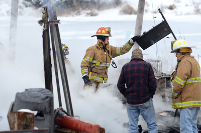 Fire fighters remove debris from a barn fire on State Road in Dornsife on Tuesday afternoon.