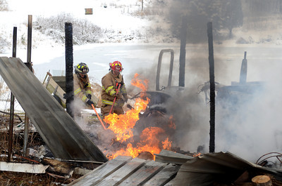 Fire fighters attempt to extinguish flames during a barn fire on State Road in Dornsife on Tuesday.