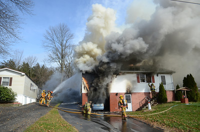 Heavy smoke and flames engulf this home on Duke Street in Point Township Thursday morning as fire fighters pour water onto the home in their attempt to put out the fire.