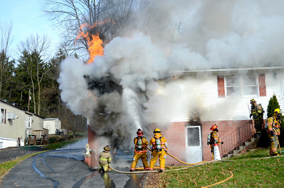 Heavy smoke and flames come from the garage area at a home on Duke Street in Point Township Thursday morning as fire fighters pour water onto the home in their attempt to put out the fire.