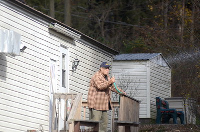 Bob Ciotti,a neighbor of the home at 2058 Duke Street in Point Township tries to help fire fighters by spraying water onto the fire that engulfed his neighbors house on Thursday morning.
