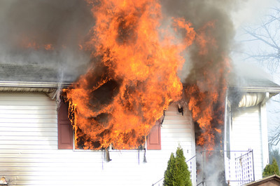 Flames shoot out the window and front door of this home on Duke Street in Point Township on Thursday morning.