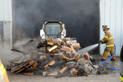 A firefighter sprays water on a pile of burnt fire wood that was pushed out of a Kuhns Brothers facility in Snyder County on Wednesday evening after a fire broke out at the facility.