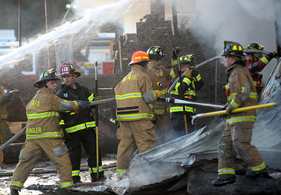 Firefighters from Union, Snyder and Northumberland Counties battle to control a fire at Kuhns Brothers' Log Homes in Lewisburg Thursday Aug. 30, 2012.