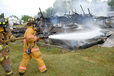 Fire fighters spray down hot spots from a barn fire in McClure on Wednesday morning just off of Route 522.
