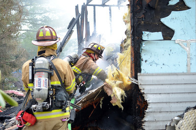 A fire fighter looks through debris of a house that caught fire on Wednesday afternoon in Point Township.