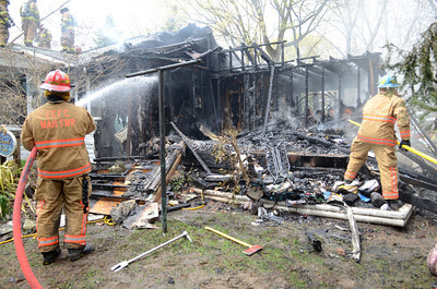 Fire fighters spray water and put out hot spots at a fire in Point Township on Wednesday afternoon.