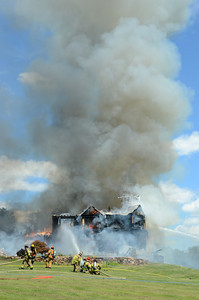 Fire fighters pour water onto a house at 200 Dogwood Road in Point Township after it caught fire on Monday afternoon.