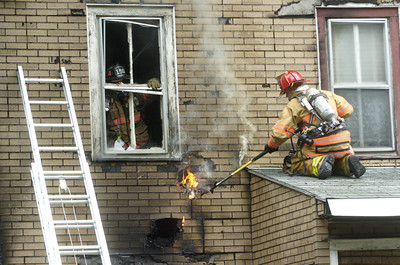 Fire fighters work to extinguish a patch of flames in the siding of a home in Shamokin that was heavily damaged by fire on Saturday.