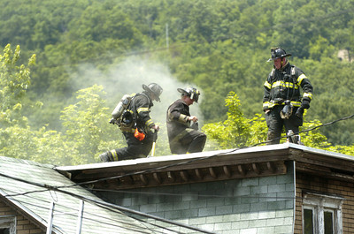 Fire fighters work on the roof of a home in Shamokin that caught fire early Saturday afternoon.