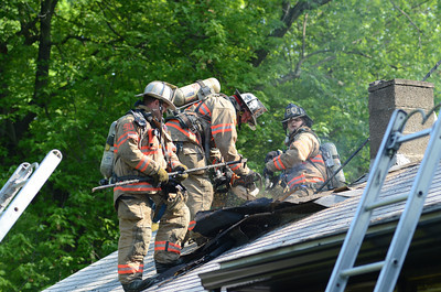 Fire fighters cut open a section of roof to gain access to hot spots at a house fire along South River Breeze Drive in Winfield on Tuesday morning.
