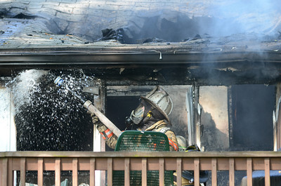 A fire fighter sprays water onto a house along South River Breeze in Winfield on Tuesday morning where a fire broke out.