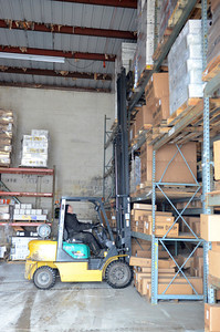 Kirk Wood uses a fork lift to stack some of the warehouse shelves at Kellers Marine in Port Trevorton on Monday.