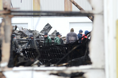 Workers help with the cleanup on Monday from the fire that heavily damaged Kellers Marine on Friday.