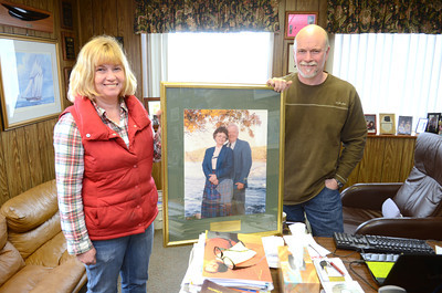 Lori Morrow and Michael Keller hold up a photo of their parents, the founders of Kellers Marine in Port Trevorton, that they were able to pull out of their office before a fire consumed it on Friday.