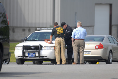 Special Agents look over paperwork outside Minuteman Environmental Services in Milton on Wednesday morning.