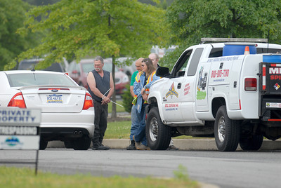 Three people in zip tie hand cuffs stand in the driveway to Minuteman Environmental Services in Milton on Monday.