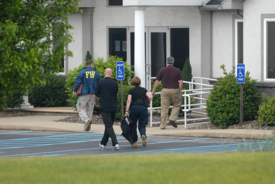 Agents from different govermental agencies including the FBI and IRS make their way into Minuteman Environmental Services in Milton on Wednesday morning.