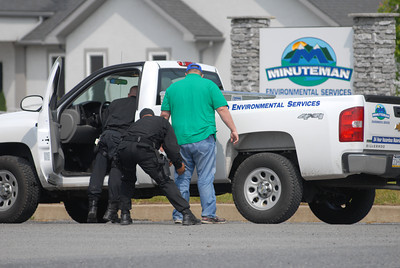 A employee of Minuteman Environmental Services is frisked outside his truck after pulling into the companies driveway on Wednesday morning.