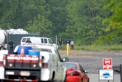 Federal agents stand in the back lot of Minuteman Environmental Services in Milton on Wednesday morning.