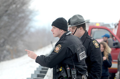 State Police officers look out over the Susquehanna River north of Port Trevorton as fire fighters searched for a person after a caller reported seeing someone out on the ice.
