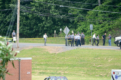Officers stand on Mile Post Road as they investigate a shooting on Tuesday afternoon.