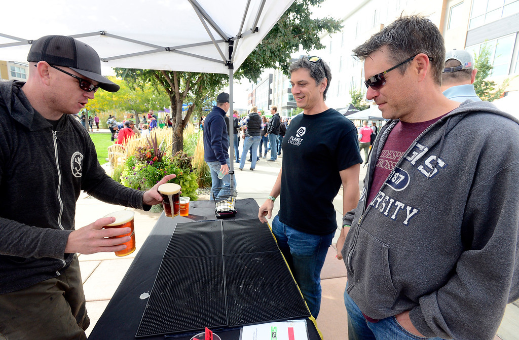 . BROOMFIELD, CO OCTOBER 6 2018 Frolic Brewing owner Chris Miser passes over two beers to Lyle Monzyk and David Kindrachuk, at right, at BrewHaHa in Broomfield on Saturday.  (Photo by Paul Aiken/Staff Photographer)