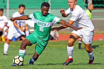 Emanuel Vl (left) from Brick gets his foot on the ball as Brick Township High School takes on Monmouth Regional High School in a boys varsity soccer game in Brick on Tuesday August 3, 2019.  (MARK R. SULLIVAN THE OCEAN STAR)