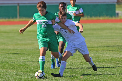 Joy Valdovinos (left) from Brick battles with Ryan Kuldanek (right) as Brick Township High School takes on Monmouth Regional High School in a boys varsity soccer game in Brick on Tuesday August 3, 2019.  (MARK R. SULLIVAN THE OCEAN STAR)