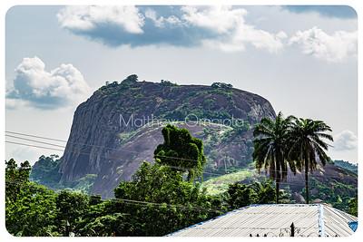 Ekiti Hills , dark rock with few vegetation on top along Ado Ekiti Iyin Ekiti road.