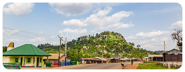 This mountain is the highest point along a mountain range on the Iyin Ado Ekiti road. It has many boulders surrounding it. Some housing development along the road.
