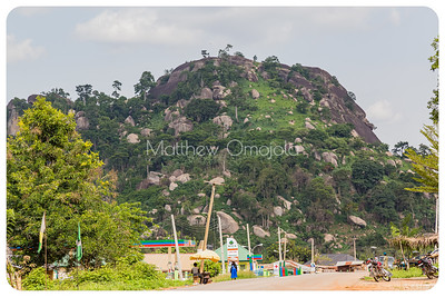 This mountain is the highest point along a ridge on the Iyin Ado Ekiti road. It has many boulders surrounding it. Some housing development at the foot hill.