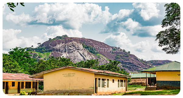 Sprawling almost bald rock looking like a huge whale along the Ado Ekiti Iyin Ekiti road. There is a school at the foothill. Editorial Photo.