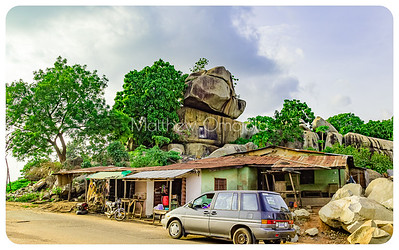 Multiple boulders on top of each other with a row of stalls at the foothill. 'Okuta gbokuta lori' at Okeyinmi area of in Ado Ekiti' Editorial photo.
