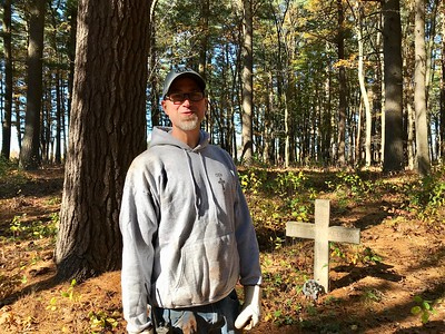 Tom Marshall stood in the Pines Cemetery where he stumbled upon forgotten graves several years ago. Restoring the cemetery is now his passion. Photo by Mary Leach