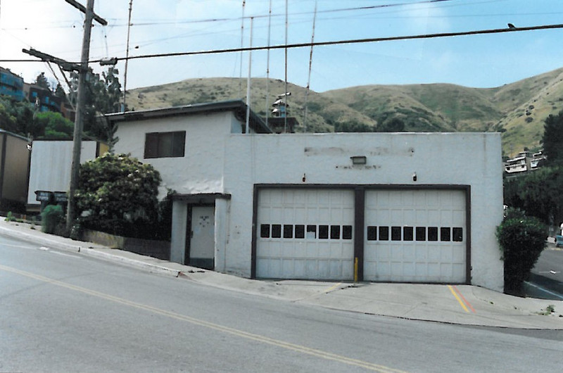 Old Fire Station #1, from across San Bruno Avenue. <br /> <br /> Glen Park Way is visible at the right, and the two trailers that were grafted on to expand the station are at the left. The horn is on top. Above the front entry door is the window to the dorm room. The roof bristles with radio antennae, with a flagpole at the front. The two apparatus bays were barely long enough for two engines end-to-end, so when the Department bought the American LaFrance enclosed-cab unit, one of the early open-cab Coast engines sat back in reserve position (it was later moved to Station 2, in the rail yard) to make space available for storage and training - and for the Police - here in the main station). There was another engine, a tanker-pumper that the Department had made up themselves on an old milk-truck chassis, that lived outside on a pad up beyond the trailers.<br /> <br /> This photo was taken after operations had been moved to the new firehouse across from Crocker Industrial Park.