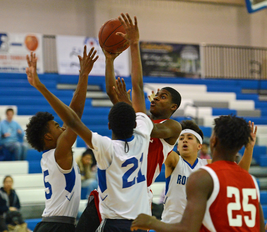. Alex Jerbo (1) drives over  Cameron Simms (5) and Hemidou Doumbie (21).
