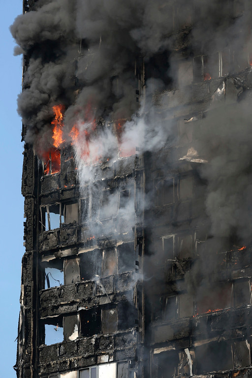 . Smoke and fire raise from a high-rise apartment building on fire in west London Wednesday, June 14, 2017. Fire swept through the high-rise apartment building early Wednesday, sending dozens people to area hospitals.  (Jonathan Brady/PA via AP)