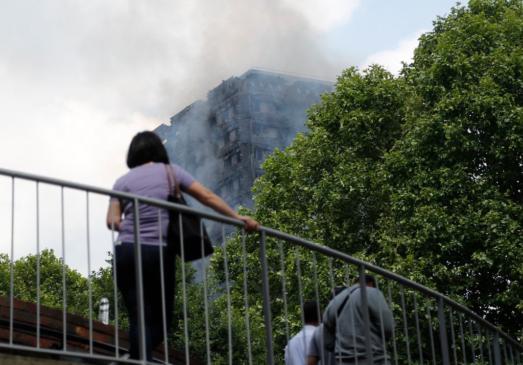 . The high-rise apartment building where a massive fire raged smoulders as people cross a pedestrian bridge nearby, in London, Wednesday, June 14, 2017. A deadly overnight fire raced through a 24-story apartment tower in London on Wednesday, killing at least six people and injuring more than 70 others. (AP Photo/Frank Augstein)