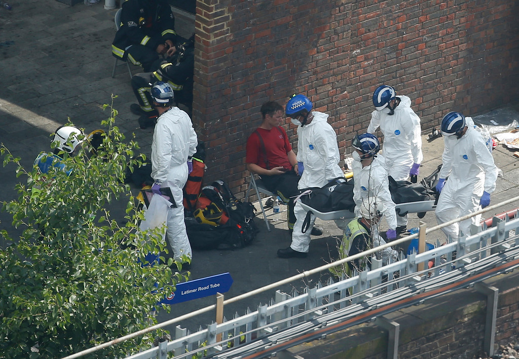 . Forensic teams move a body near the scene of a fire at a high rise apartment block, in London, Wednesday, June 14, 2017. Firefighters are battling a huge blaze at a west London high-rise block that houses more than 100 apartments. (AP Photo/Alastair Grant)
