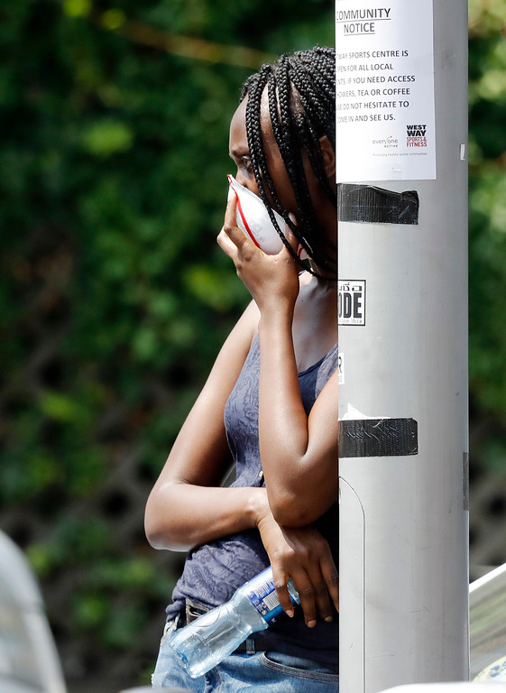 . A woman covering her face with a mask for protection from the smoke, stands near the high-rise apartment building where a massive fire raged, in London, Wednesday, June 14, 2017. A deadly night-time fire raced through a 24-story apartment tower in London early Wednesday, killing at least six people and injuring dozens more. (AP Photo/Frank Augstein)