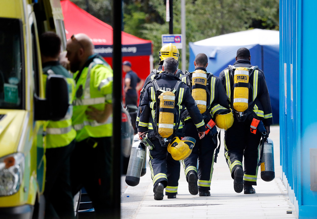 . Emergency services attend the scene of the high-rise apartment building where a massive fire raged overnight, in London, Wednesday, June 14, 2017. A deadly overnight fire raced through a 24-story apartment tower in London on Wednesday, killing at least six people and injuring more than 70 others. (AP Photo/Frank Augstein)