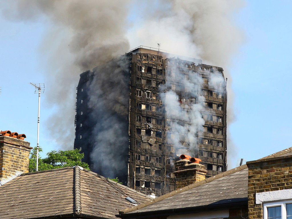 . Smoke billows from from a high-rise apartment building on fire in London, Wednesday, June 14, 2017. A massive fire raced through the 27-story high-rise apartment building in west London early Wednesday, sending at least 30 people to hospitals, emergency officials said. (Rick Findler/PA via AP)