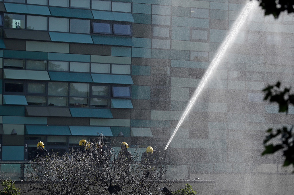 . Firefighters battle a massive fire that raged in a 27-floor high-rise apartment building in London, Wednesday, June 14, 2017. Fire swept through a high-rise apartment building in west London early Wednesday, killing an unknown number of people and sending more than 50 people to area hospitals. (AP Photo/Matt Dunham)