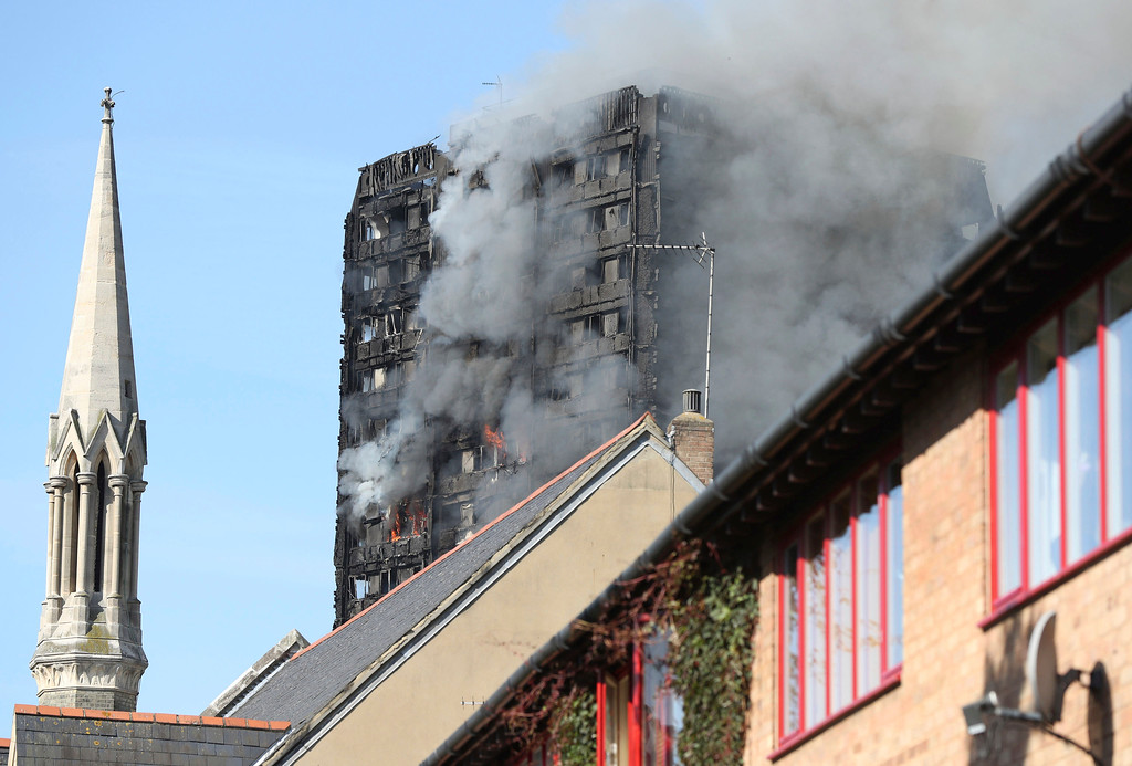 . Smoke billows from a high-rise apartment building on fire in west London Wednesday, June 14, 2017. Fire swept through the high-rise apartment building early Wednesday, sending dozens people to area hospitals. (Jonathan Brady/PA via AP)