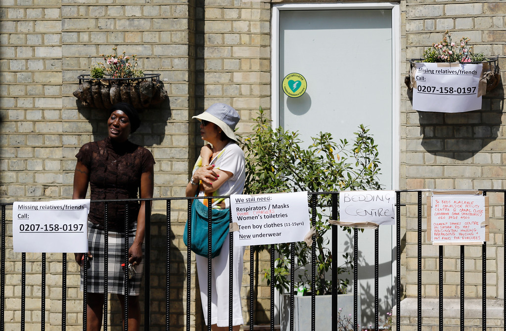 . People stand outside a center offering emergency supplies near the high-rise apartment building where a massive fire raged overnight, in London, Wednesday, June 14, 2017. A deadly overnight fire raced through a 24-story apartment tower in London on Wednesday, killing at least six people and injuring more than 70 others. (AP Photo/Frank Augstein)