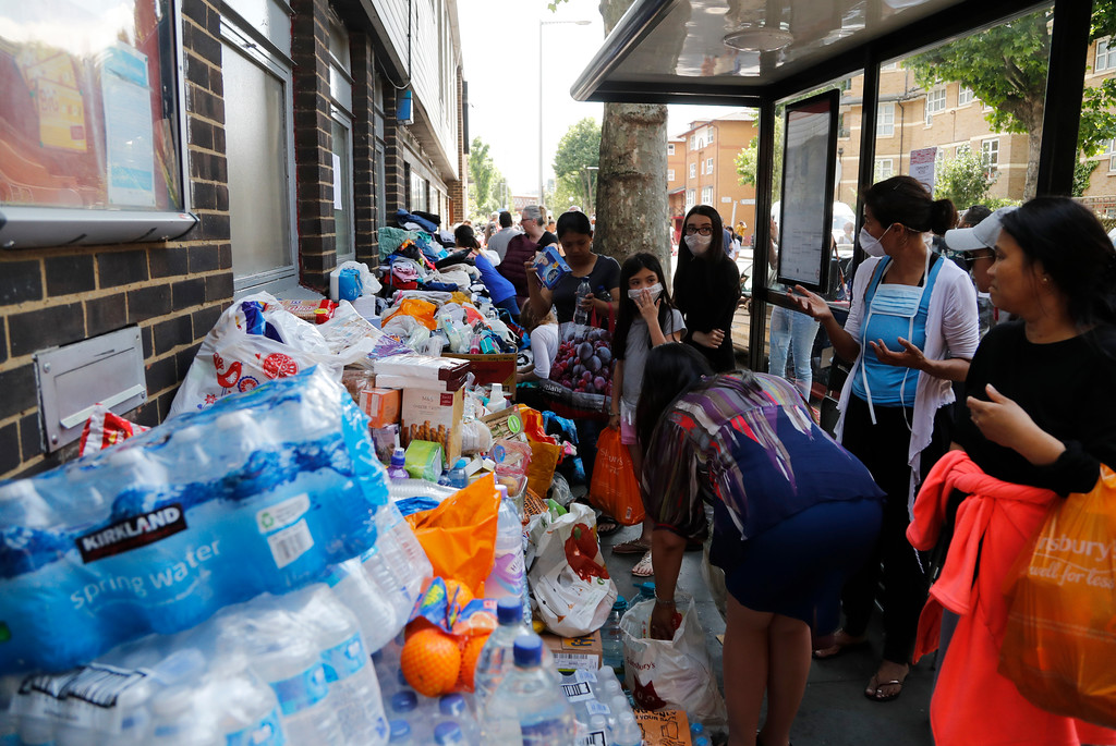 . Emergency supplies are offered near to the high-rise apartment building where a massive fire raged, in London, Wednesday, June 14, 2017. A deadly overnight fire raced through a 24-story apartment tower in London on Wednesday, killing at least six people and injuring more than 70 others. (AP Photo/Frank Augstein)