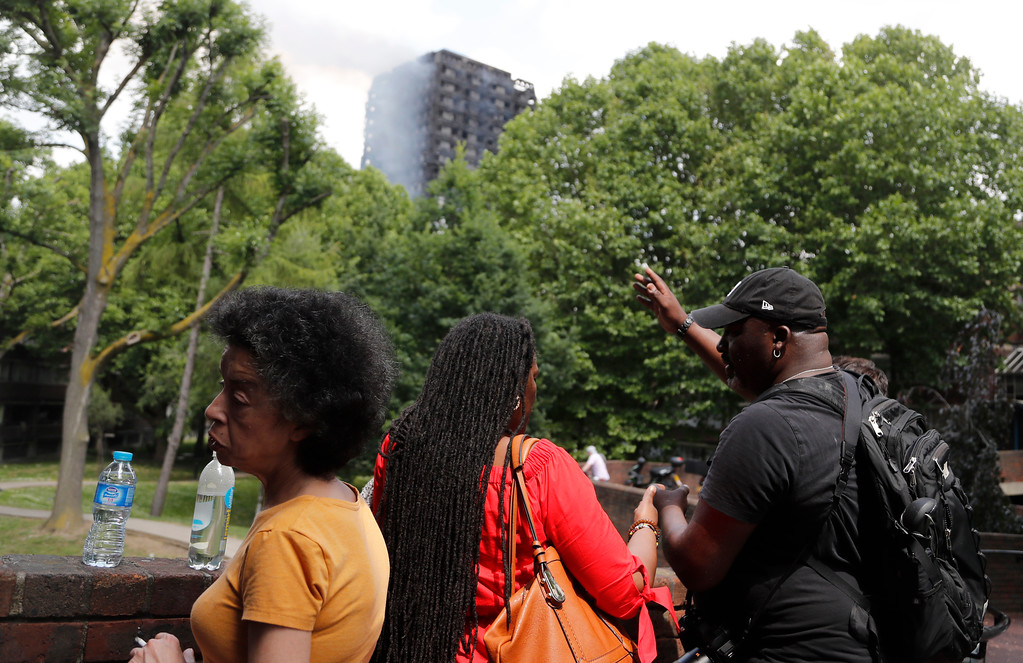 . People nearby look at the high-rise apartment building where a massive fire raged, in London, Wednesday, June 14, 2017. A deadly overnight fire raced through a 24-story apartment tower in London on Wednesday, killing at least six people and injuring more than 70 others. (AP Photo/Frank Augstein)