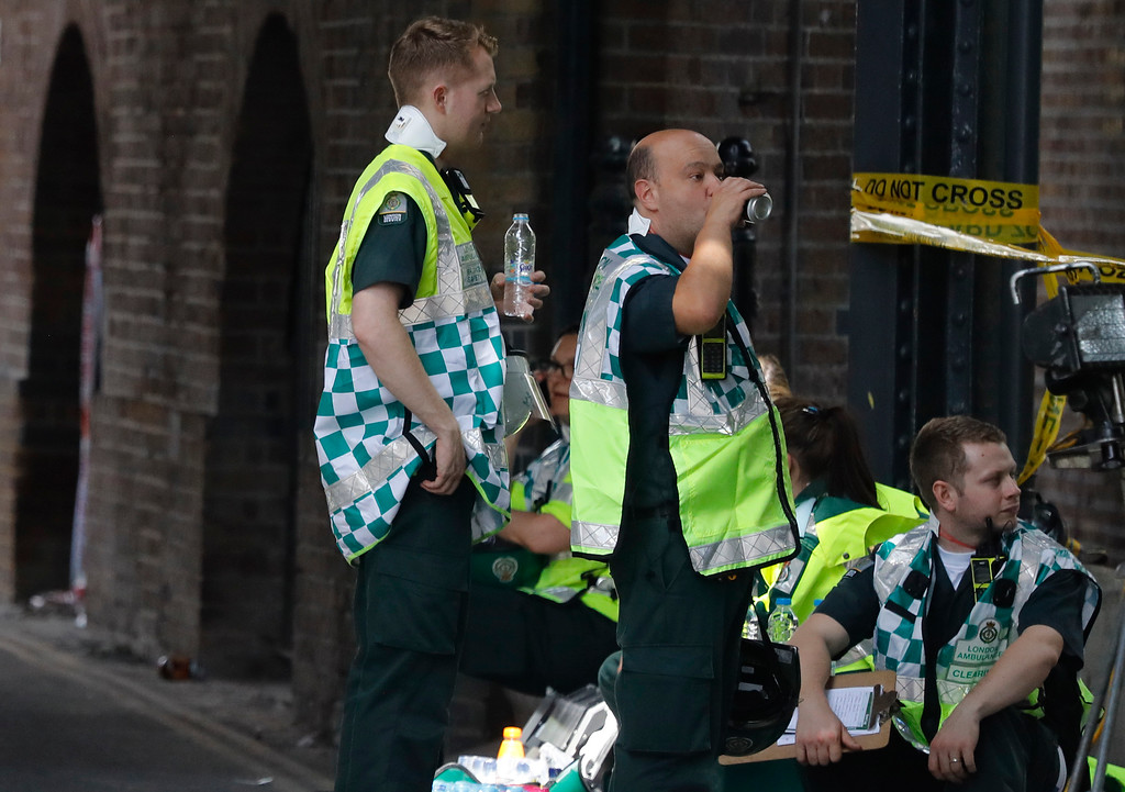 . Emergency services personnel take a break near to the high-rise apartment building where a massive fire raged, in London, Wednesday, June 14, 2017. A deadly overnight fire raced through a 24-story apartment tower in London on Wednesday, killing at least six people and injuring more than 70 others. (AP Photo/Frank Augstein)
